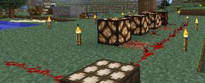 Изображён датчик дневного света, подключённый к индикатору мощности, на фоне тайги, постройки из серого блока (возможно булыжника) и другой схемы из красного камня.